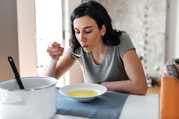 Young woman eating bone broth.