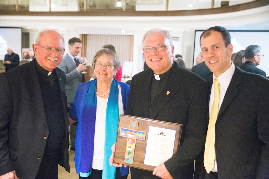 Fr. Michael J. Garanzini, S.J., [center right] with Fr. Fred Kammer, S.J., ISN Board Chair; Loretta Holstein, wife of the late Robert Holstein; and Christopher Kerr, ISN executive director (Photo: Ian Frendreis)