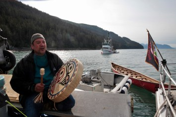John Garcia plays a song for his fellow paddlers on Wednesday, June 8, 2016, near Juneau, Alaska. The One People Canoe Society group began the trip to Juneau from Angoon on June 2. Their landing on Douglas Island is the unofficial beginning of Celebration. (Photo by Rashah McChesney/KTOO)