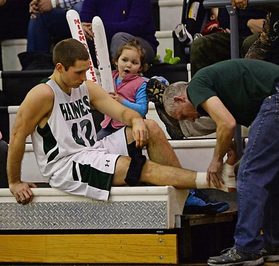 Kake basketball fan Annie Vernetti, 4, talks to Haines guard Kyle Fossman as his coach, and father, Steve Fossman tapes his ankle during Haines' 82-52 win over Wrangell in B-Bracket action at the Juneau Lions Club 71st Annual Gold Medal Basketball Tournament on Monday. Haines won 82-52. (Photo courtesy Klas Stolpe)