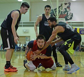 Kake's Deion Jackson protects the ball from Angoon defenders during their B-Bracket elimination game in the Juneau Lions Club 71st Annual Gold Medal Basketball Tournament at Juneau-Douglas High School on Wednesday. Angoon won 96-75. (Photo courtesy Klas Stolpe)