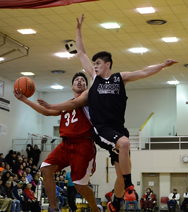 Kake's Lance Doake (32) is defended by Angoon's Duncan O'Brien (34) during their B-Bracket elimination game in the Juneau Lions Club 71st Annual Gold Medal Basketball Tournament at Juneau-Douglas High School on Wednesday. Angoon won 96-75. (Photo courtesy Klas Stolpe)
