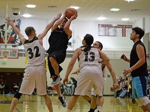 Hydaburg's Vinny Edenshaw splits the defense of Haines' Tyler Healey (32), Ryan Harms (13) and Kyle Fossman in B-bracket action at the Juneau Lions Club 71st Annual Gold Medal Basketball Tournament on Sunday, March 19, 2017, at JDHS. Haines won 86-71. (Photo courtesy Klas Stolpe)