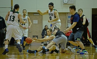 Haines' Kyle Fossman passes a loose ball under pressure from Wrangell's Andrew Versteeg during their B-Bracket quarterfinal in the Juneau-Lions Club 71st Annual Gold Medal Basketball Tournament at Juneau-Douglas High School on Monday. (Photo courtesy Klas Stolpe)
