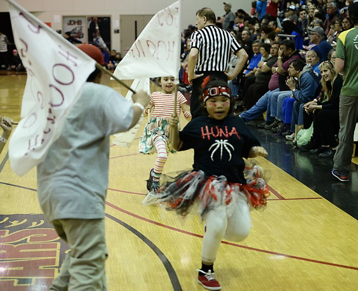 Hoonah fans run with flags during the B-Bracket semifinal in the Juneau Lions Club 71st Annual Gold Medal Basketball Tournament at Juneau-Douglas High School on Thursday. (Photo courtesy Klas Stolpe)