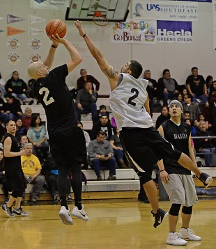 Hydaburg's Devin Edenshaw (2) scores over Metlakatla's Brian Hayward (2) during their B-Bracket elimination game at the Juneau Lions Club 71st Annual Gold Medal Basketball Tournament at Juneau-Douglas High School on Tuesday. Hydaburg won 96-88. (Photo courtesy Klas Stolpe)