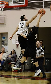 Metlakatla's Joshua O'Brien (18) blocks a shot by Hydaburg's Greg Frisby (3) during their B-Bracket elimination game at the Juneau Lions Club 71st Annual Gold Medal Basketball Tournament at Juneau-Douglas High School on Tuesday. Hydaburg won 96-88. (Photo courtesy Klas Stolpe)