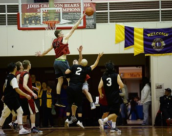 Wrangell's Ryan Reeves blocks a shot by Hydaburg's Devin Edenshaw (2) during a B-Bracket elimination game in the Juneau Lions Club 71st Annual Gold Medal Basketball Tournament at Juneau-Douglas High School on Wednesday. Wrangell won 87-68. (Photo courtesy Klas Stolpe)