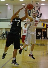 Angoon's Levi Johnson Sr. (4) and Hoonah's Michael Schneeberger (33) battle for a rebound during their C-Bracket elimination game at the Juneau Lions Club 71st Annual Gold Medal Basketball Tournament at Juneau-Douglas High School on Tuesday. Hoonah won 88-66. (Photo courtesy Klas Stolpe)