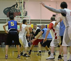 Hoonah's Travis Dybdahl looks to pass under pressure from James Gang's Jim Carson during their C-Bracket elimination game at the Juneau Lions Club 71st Annual Gold Medal Basketball Tournament at Juneau-Douglas High School on Thursday. James Gang won 71-50. (Photo courtesy Klas Stolpe)
