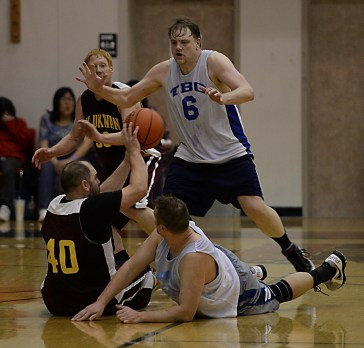 Klukwan's Stuart Dewitt (40) passes under pressure from James Gang's Ray Zimmer and Sean Joslyn (6) during C-Bracket championship of the Juneau Lions Club 71st Annual Gold Medal Basketball Tournament at Juneau-Douglas High School on Saturday. Klukwan won 107-97. (Photo courtesy Klas Stolpe)