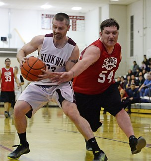 Michael Ganey (23) and Kake's Jess Ross (54) battle for a loose ball during Klukwan's 85-54 win in their opening C Bracket game of the Juneau Lions Club 71st Annual Gold Medal Basketball Tournament at JDHS on Sunday, March 19, 2017. (Photo courtesy Klas Stolpe)