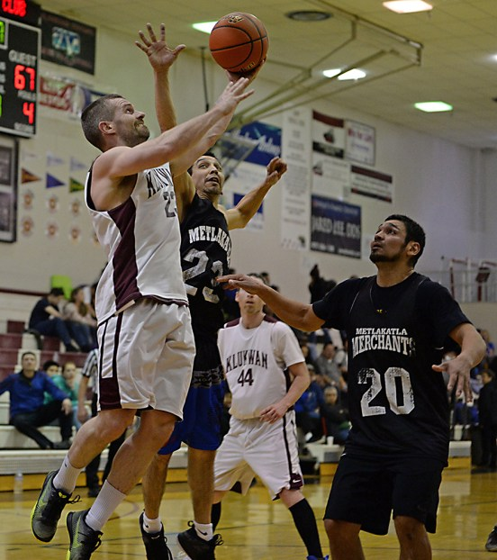 Klukwan's Michael Ganey shoots under pressure from Metlakatla's Chris Mowers (23) and Willie Hayward (20) during their C-Bracket semifinal in the Juneau Lions Club 71st Annual Gold Medal Basketball Tournament at Juneau-Douglas High School on Thursday. Klukwan won 96-94. (Photo courtesy Klas Stolpe)