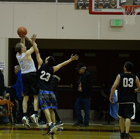 James Gang's Greg Huebschen (2) shoots over Metlakatla's Chris Mowers (23) during their C-Bracket elimination game in the Juneau Lions Club 71st Annual Gold Medal Basketball Tournament at Juneau-Douglas High School on Friday. James Gang won 84-74. (Photo courtesy Klas Stolpe)