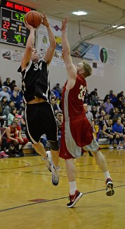 Yakutat's Jimmy Jensen (34) scores over Hoonah's Michael Schneeberger (33) in a C Bracket game of the Juneau Lions Club 71st Annual Gold Medal Basketball Tournament at JDHS on Sunday, March 19, 2017. Yakutat won 62-59. (Photo courtesy Klas Stolpe)