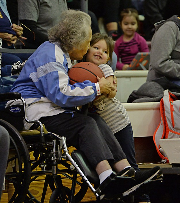Hoonah's Harriet Knudson gives granddaughter Gabriel Refuerzo, 4, a thank you kiss after a gift of a basketball at the Juneau Lions Club 71st Annual Gold Medal Basketball Tournament at Juneau-Douglas High School on Thursday. (Photo courtesy Klas Stolpe)
