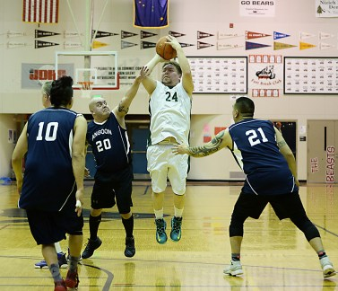 Sitka's Steve Edenshaw (24) is fouled by Angoon's Paul Johnson (20) during their Masters Bracket game of the Juneau-Lions Club 71st Annual Gold Medal Basketball Tournament at Juneau-Douglas High School on Monday. Angoon won 65-56. (Photo courtesy Klas Stolpe)