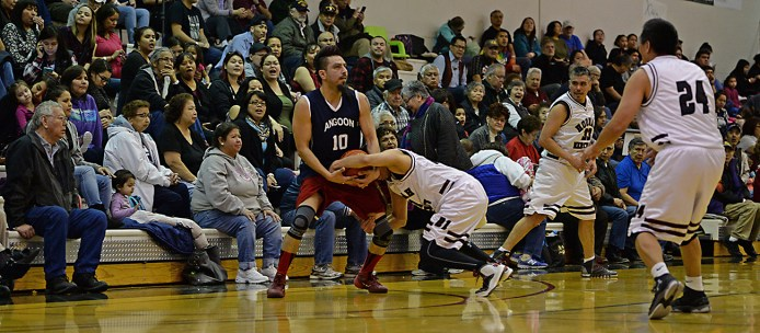 Angoon's Marti Fred (10) is wrestled on defense by Hoonah's Louie White Sr. during their Masters Bracket elimination game at the Juneau Lions Club 71st Annual Gold Medal Basketball Tournament at Juneau-Douglas High School on Thursday. Hoonah won 94-67. (Photo courtesy Klas Stolpe)