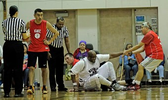 Hoonah's Tierney Bible is helped up by Kake's Mike Martin during the Master's Bracket championship of the Juneau Lions Club 71st Annual Gold Medal Basketball Tournament at Juneau-Douglas High School on Saturday. Hoonah won 80-78. (Photo courtesy Klas Stolpe)