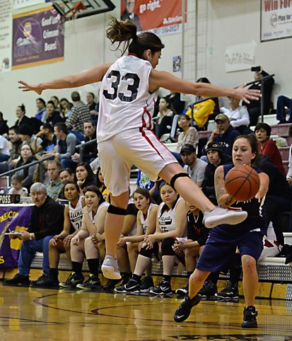 Hoonah's Krissy Bean (33) kicks a pass by Yakutat's Kim Buller (5) during their Womens Bracket elimination game in the Juneau Lions Club 71st Annual Gold Medal Basketball Tournament at Juneau-Douglas High School on Friday. Hoonah won 56-53. (Photo courtesy Klas Stolpe)