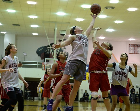 Haines' Alisa Beske (55) rebounds over Hoonah's Taryn White and Krissy Bean (33) during the Women's Bracket championship of the Juneau Lions Club 71st Annual Gold Medal Basketball Tournament at Juneau-Douglas High School on Saturday. Haines won 52-30. (Photo courtesy Klas Stolpe)