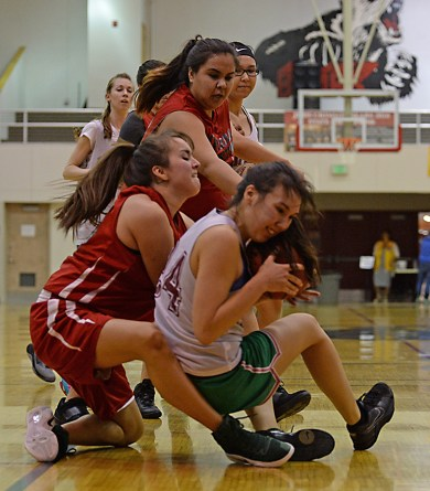Haines' Tiffany Dewitt and Hoonah's Ladonna Johnson battle for a loose ball during the Women's Bracket championship of the Juneau Lions Club 71st Annual Gold Medal Basketball Tournament at Juneau-Douglas High School on Saturday. Haines won 52-30. (Photo courtesy Klas Stolpe)