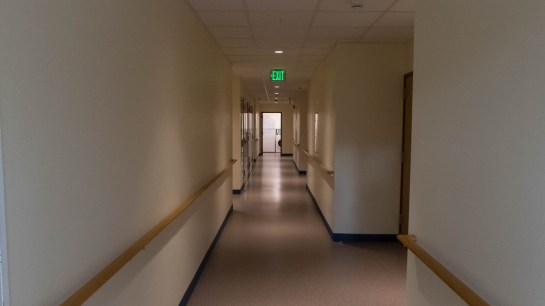 A long white hallway with doors opening off it