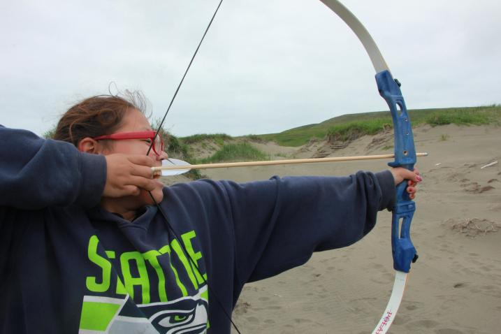 Miszenna prepares to shoot a bow into a sand dune. (Photo by Isabelle Ross/KDLG)
