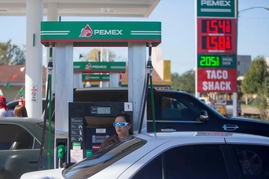 Yvette Garcia fills up with gas at the grand opening of PEMEX in the 7900 block of Park Place Blvd, Thursday, Dec. 3, 2015, in Houston. The national energy company of Mexico, Pemex, is launching its brand in the U.S. with retail gasoline stations, starting in Houston. (Cody Duty / Houston Chronicle)