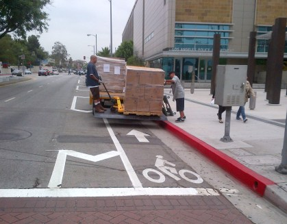 Two men unloading cargo with their vehicle parked on the bike lane.