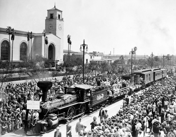 """A Union Pacific locomotive and five cars constructed for Cecil B. DeMille's """"Union Pacific"""" film travel down Alameda. Photo by Harry Quillen."""