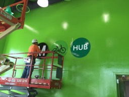 Worker installs branding on the interior wall.