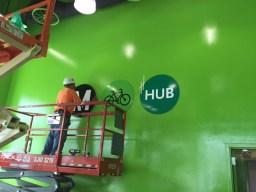 Worker installs branding on the interior wall.