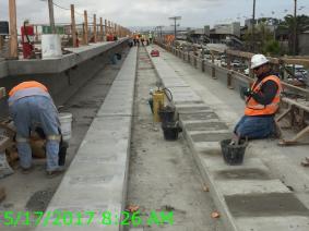 Finish work to remove surface irregularities following plinth form removals on Aviation/Century Bridge.