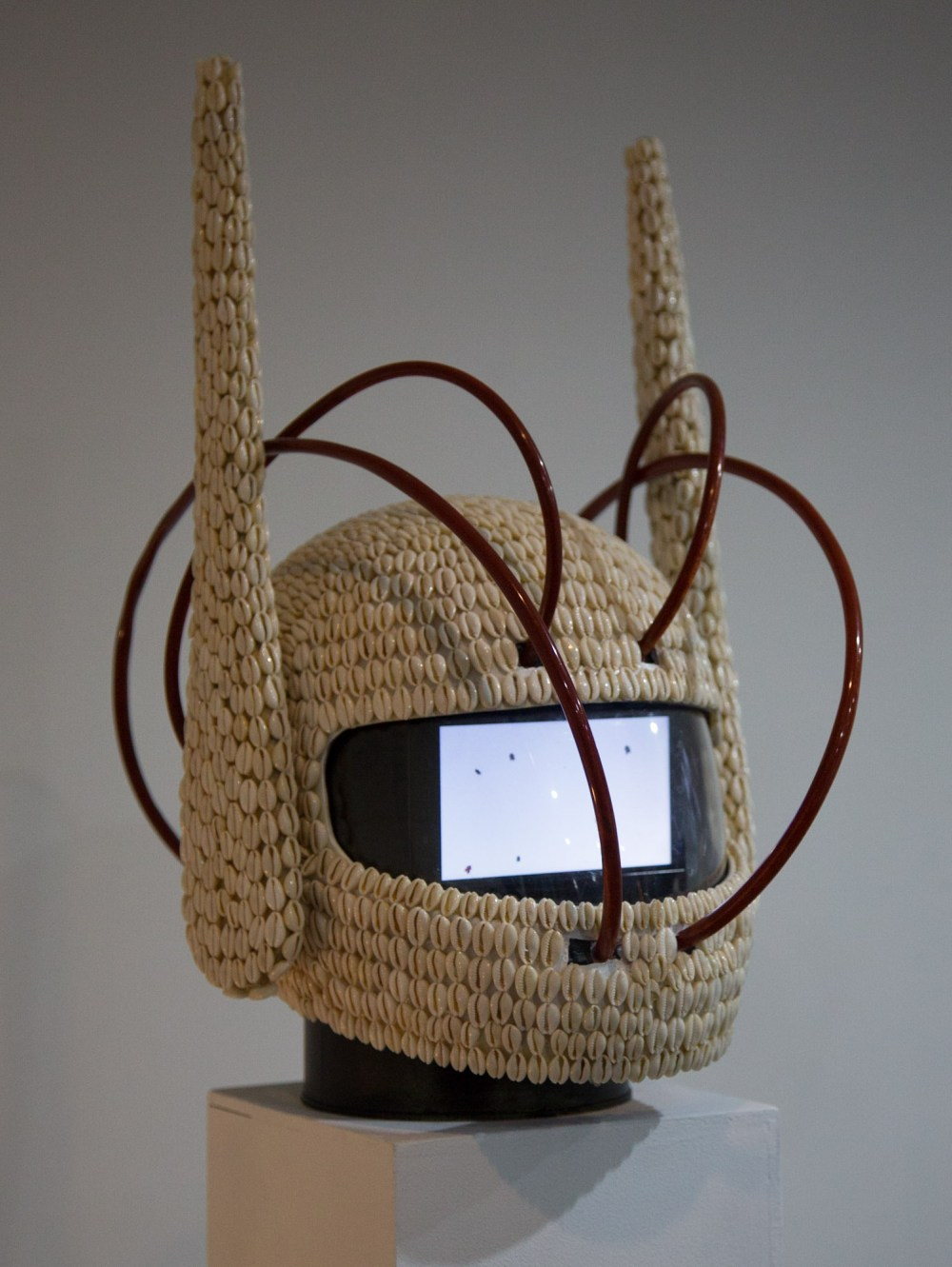 a afrofuturism piece of art, a helmet with knitted horns on it and a screen inside