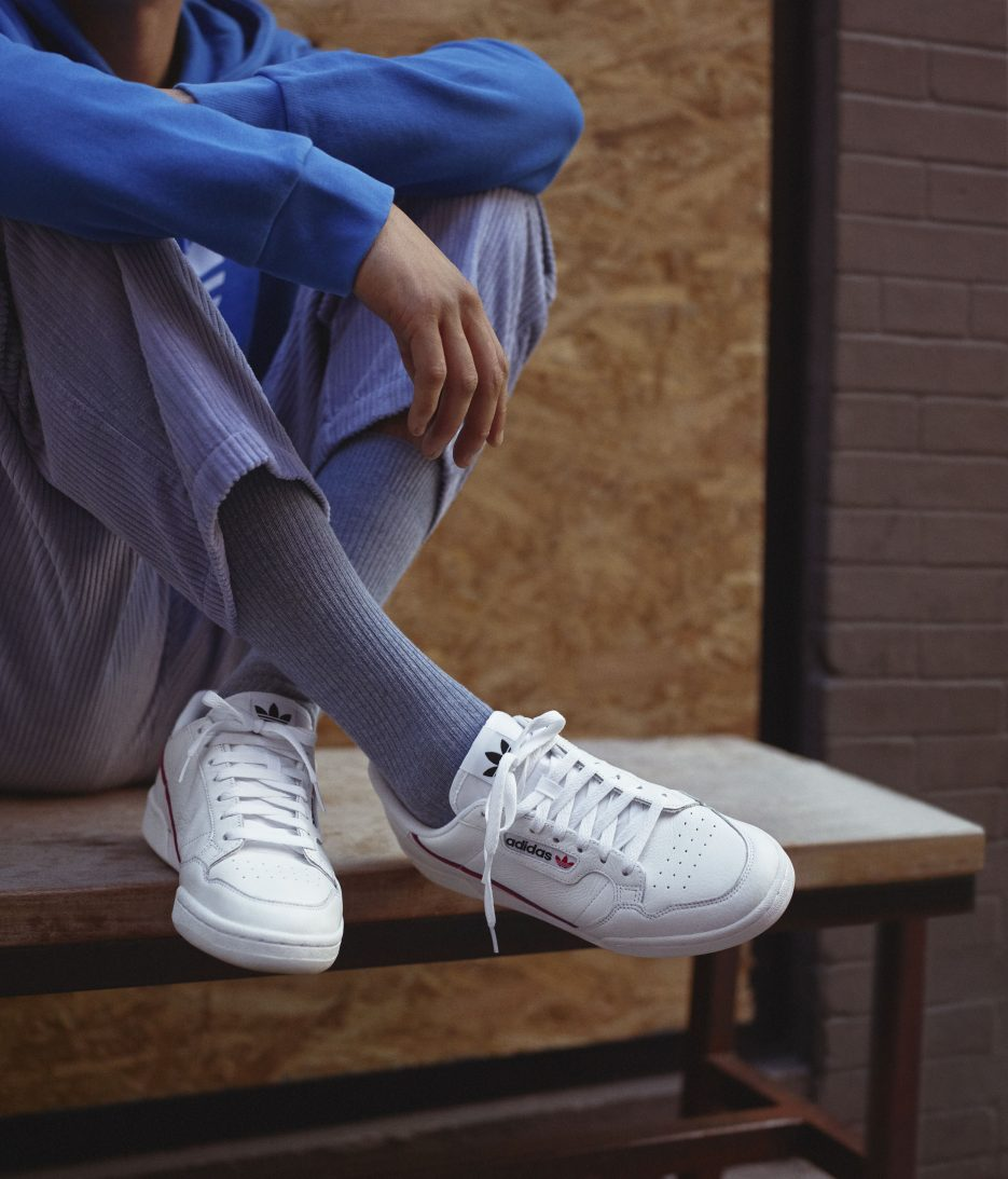 Adidas Continental 80 sneaker being worn by a person wearing grey sitting on a bench