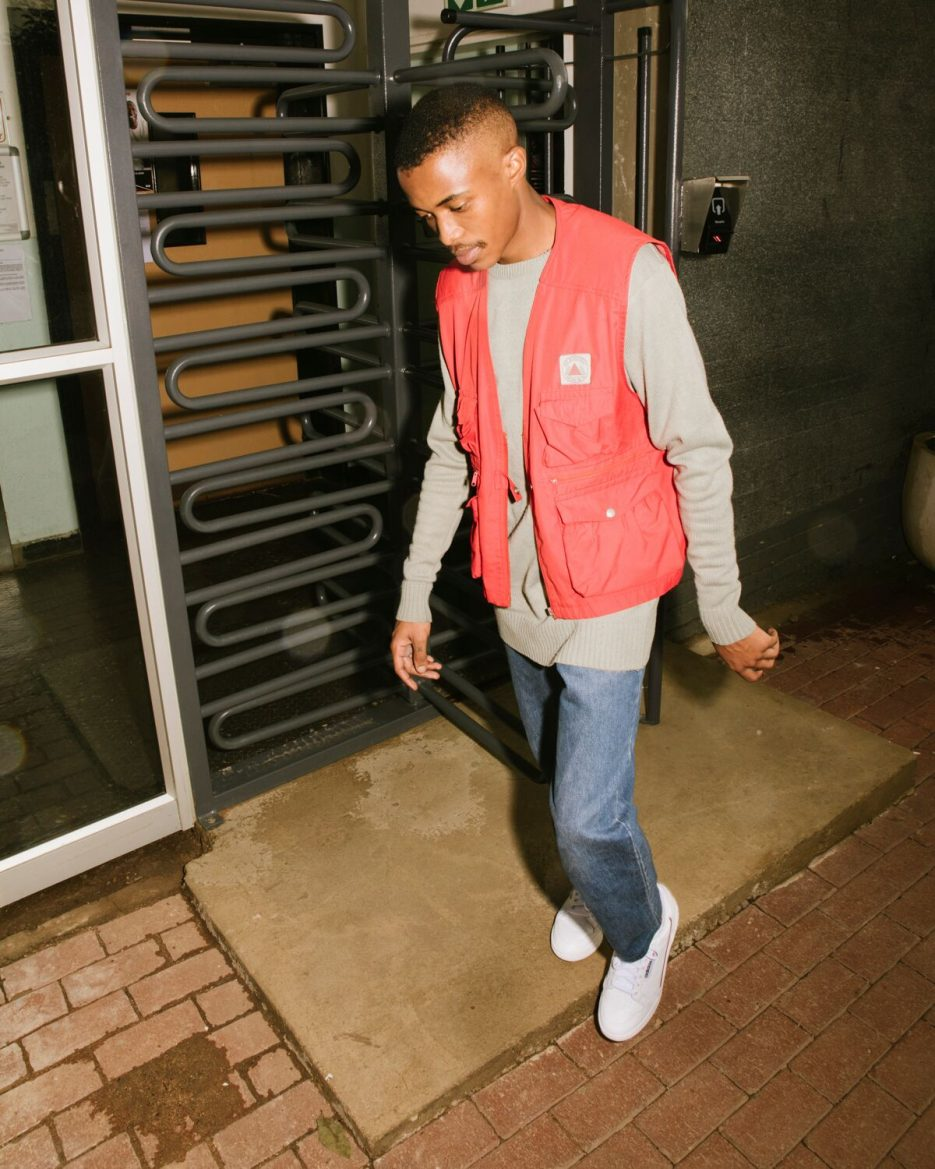 A man wearing classic denims and red overcoat with Adidas Contintental 80 sneakers.