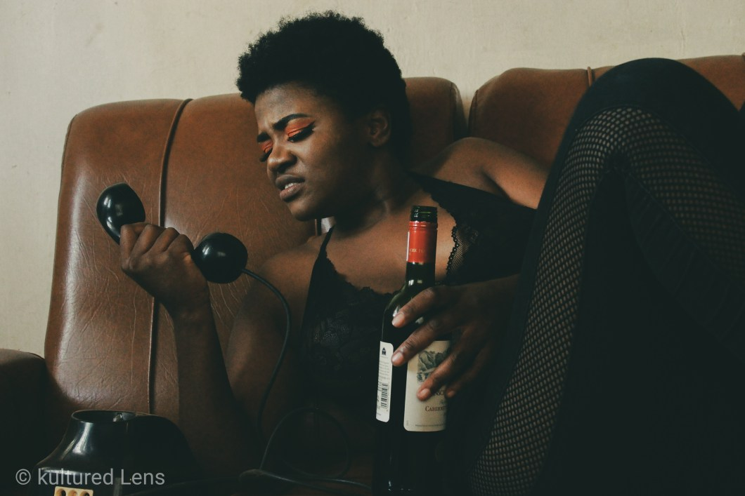 A woman lying on a couch holding a phone and bottle of wine taken by Kultured Lens