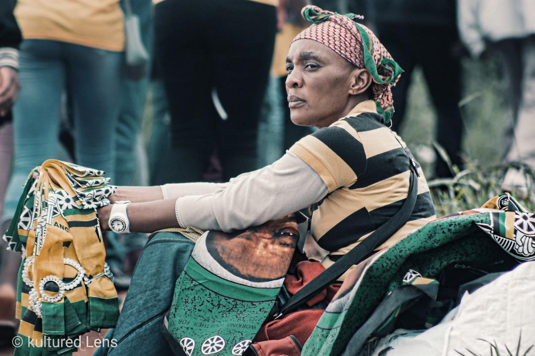 A woman sitting down selling regalia taken by Karabo Maila