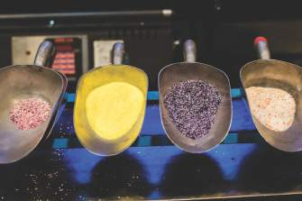 """glass particles called """"frit"""" wait in scoops to become the coloring of glass art"""
