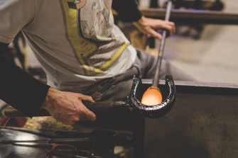 Hugh Willa; Hugh is using steam from water-soaked hardwood block to smooth the shape of the molten glass