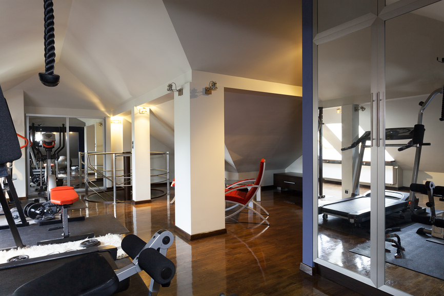 Luxury home gym with treadmill and free weights with mirrors on wall and wood floors
