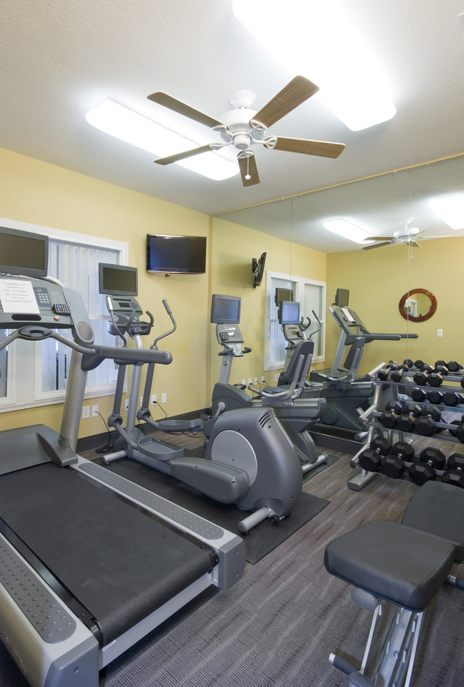 Small home exercise studio with treadmill, elliptical trainer and weights with ceiling fan
