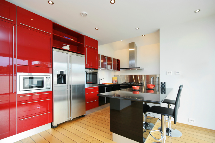 Small red kitchen with black island and light hard wood flooring