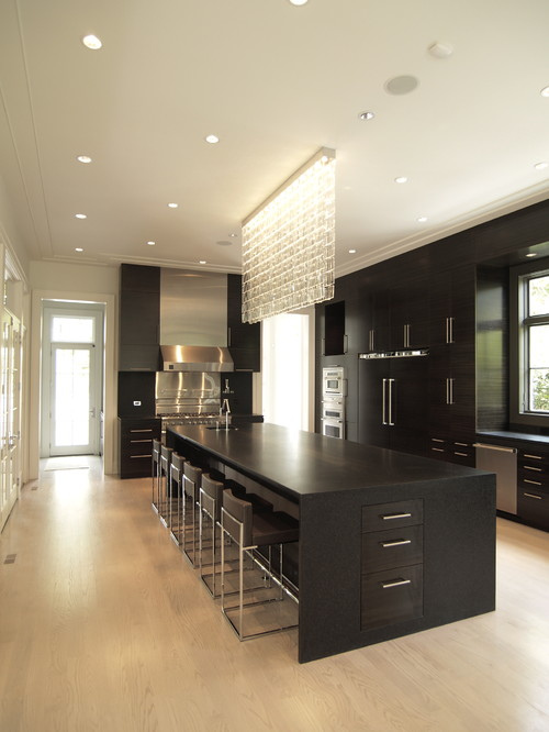 Photograph of modern kitchen with black island and cabinets and light wood flooring