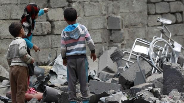 Niños observan los restos de un bombardeo en Sanaa, capital de Yemen (AFP)