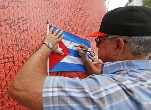 El fanático Juan De Feria escribeun mensaje para Fernández en una bandera cubana (AP)