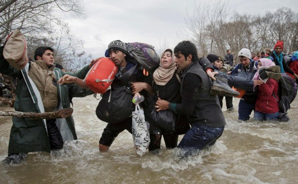 Asuntos Contemporáneos, segundo premio. El cruce de los inmigrantes. Una mujer recibe el apoyo de dos hombres mientras cruzan un río en el intento por alcanzar Macedonia por una ruta que esquiva la seguridad fronteriza. Vadim Ghirda, The Associated Press