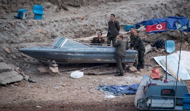 Soldados norcoreanos descansan junto a un bote a las orillas del río (Fotos: AFP)