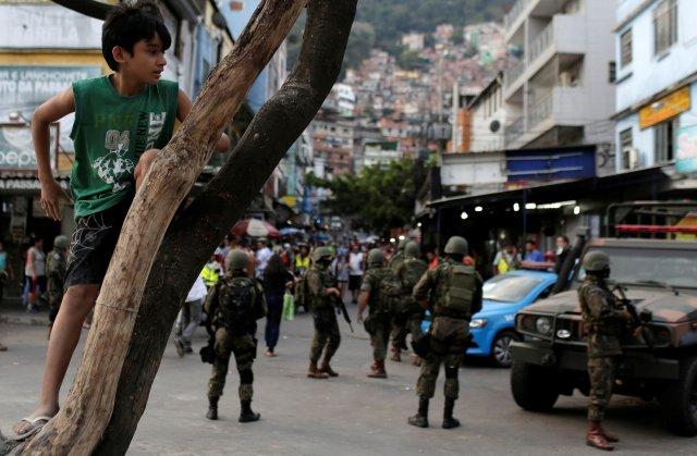 Un niño juega mientras militares recorren la favela (Reuters)